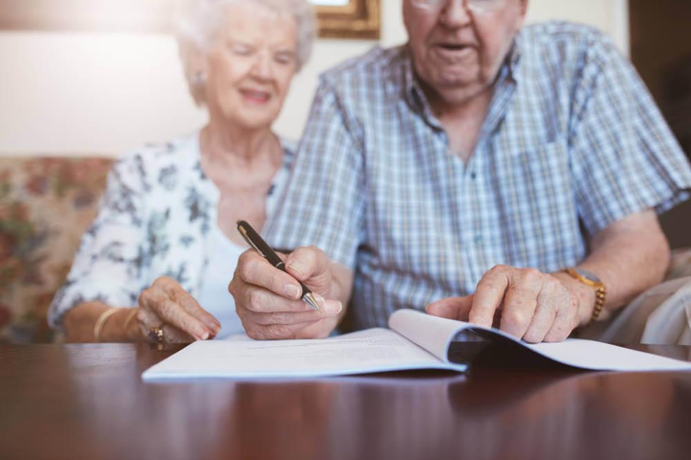 elderly-couple-signing-important-document