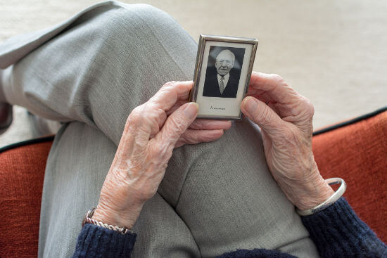 senior-lady-looking-at-image-of-deceased-loved-one