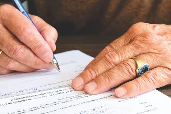 elderly-man-signing-document